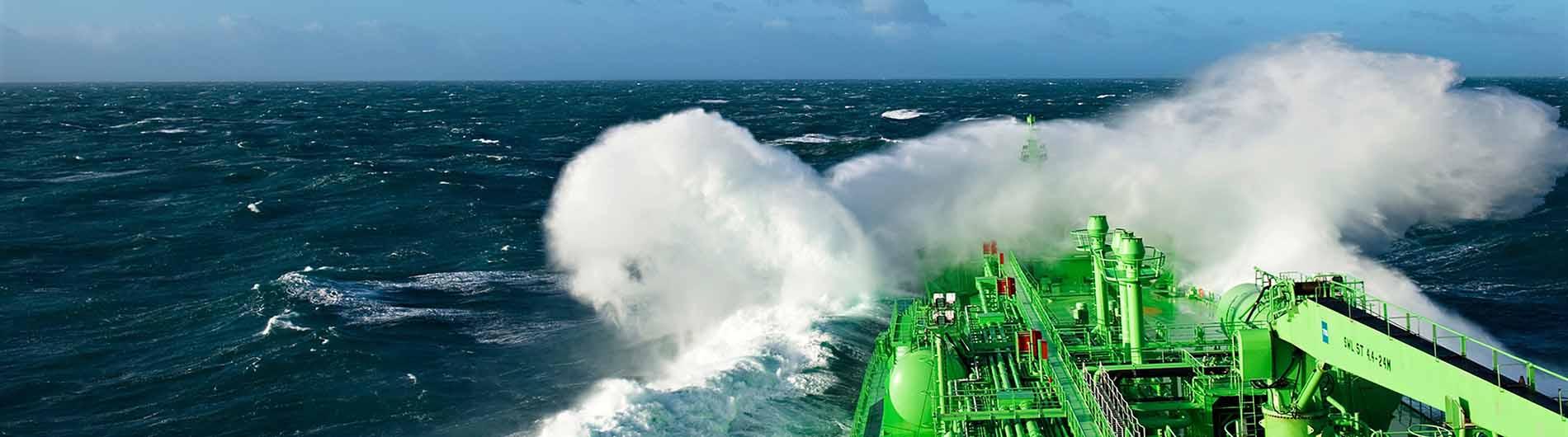 Green Vessel at sea in big waves